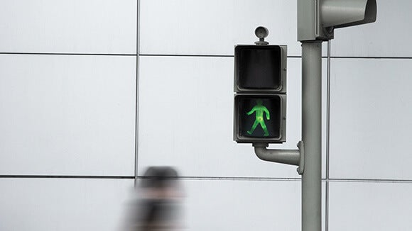 Electronic crosswalk sign on metal post with safe to cross signal