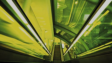 Escalator stairs going up in futuristic tunnel with bright, vivid green colors light
