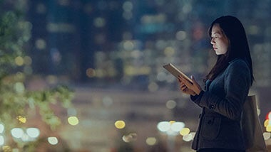 Asian woman looking at her tab while standing with city lights background