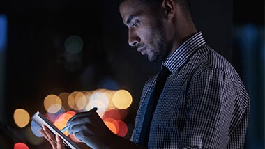 A man looking at tablet with city lights background